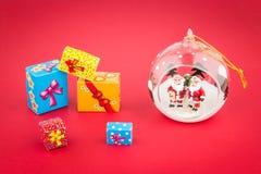Прозрачный шарик рождества с внутренностью и подарочными коробками Santas Стоковая Фотография RF
