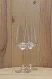 2 прозрачных стекла стоя на деревянной стойке с деревянной предпосылкой Стоковые Фотографии RF