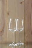 2 прозрачных стекла стоя на стеклянной стойке с деревянной предпосылкой Стоковые Фотографии RF