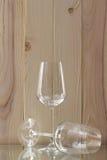 2 прозрачных стекла стоя на стеклянной стойке с деревянной предпосылкой Стоковая Фотография