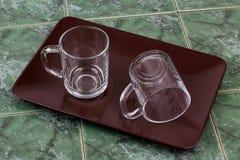 2 прозрачных чашки на коричневой плите Стоковое фото RF