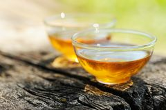 2 прозрачных чашки черного чая на старой деревянной доске в яркой Стоковое Изображение RF