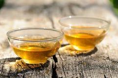 2 прозрачных чашки черного чая на старой деревянной доске в яркой Стоковая Фотография