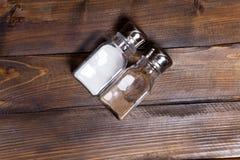2 прозрачных чонсервной банкы шейкера соли и перца на деревянной предпосылке Стоковые Фото