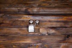 2 прозрачных чонсервной банкы шейкера соли и перца на деревянной предпосылке Стоковое Изображение RF