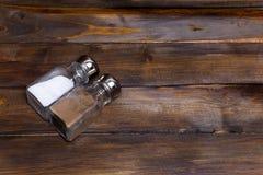 2 прозрачных чонсервной банкы шейкера соли и перца на деревянной предпосылке Стоковое Изображение