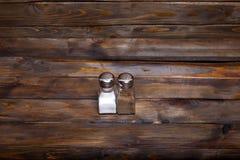 2 прозрачных чонсервной банкы шейкера соли и перца на деревянной предпосылке Стоковые Фотографии RF