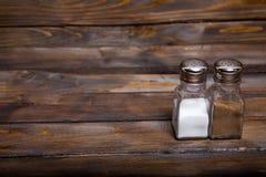 2 прозрачных чонсервной банкы шейкера соли и перца на деревянной предпосылке Стоковая Фотография