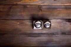 2 прозрачных чонсервной банкы шейкера соли и перца на деревянной предпосылке Стоковое Фото