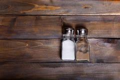 2 прозрачных чонсервной банкы шейкера соли и перца на деревянной предпосылке Стоковое фото RF