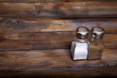 2 прозрачных чонсервной банкы шейкера соли и перца на деревянной предпосылке Стоковые Изображения