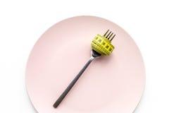проигрышный вес диетпитание строгое Пустая плита и измеряя лента на еде вилки вместо на белом модель-макете взгляд сверху предпос Стоковая Фотография