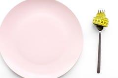 проигрышный вес диетпитание строгое Пустая плита и измеряя лента на еде вилки вместо на белом модель-макете взгляд сверху предпос Стоковое фото RF