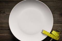 проигрышный вес диетпитание строгое Пустая плита и измеряя лента на еде вилки вместо на деревянном модель-макете взгляд сверху пр Стоковая Фотография