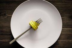 проигрышный вес диетпитание строгое Пустая плита и измеряя лента на еде вилки вместо на деревянном модель-макете взгляд сверху пр Стоковое Изображение