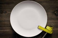 проигрышный вес диетпитание строгое Пустая плита и измеряя лента на еде вилки вместо на деревянном модель-макете взгляд сверху пр Стоковое фото RF