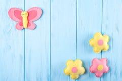 Произведите розовые и желтые бабочку и цветки с белой бумагой, copyspace на голубой деревянной предпосылке Ручной работы игрушки  Стоковые Изображения
