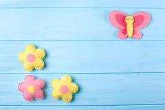 Произведите розовые и желтые бабочку и цветки с белой бумагой, copyspace на голубой деревянной предпосылке Ручной работы игрушки  Стоковое Фото