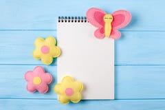 Произведите розовые и желтые бабочку и цветки с белой бумагой, copyspace на голубой деревянной предпосылке Ручной работы игрушки  Стоковая Фотография