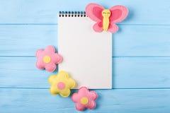 Произведите розовые и желтые бабочку и цветки с белой бумагой, copyspace на голубой деревянной предпосылке Ручной работы игрушки  Стоковое Изображение RF