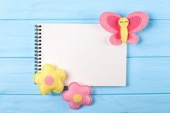 Произведите розовые и желтые бабочку и цветки с белой бумагой, copyspace на голубой деревянной предпосылке Ручной работы игрушки  Стоковое фото RF