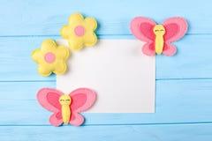 Произведите розовые и желтые бабочку и цветки с белой бумагой, copyspace на голубой деревянной предпосылке Ручной работы игрушки  Стоковые Фотографии RF