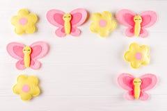 Произведите розовые и желтые бабочку и цветки, copyspace на белой деревянной предпосылке Ручной работы игрушки войлока абстрактно Стоковые Изображения RF