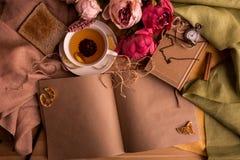 Произведите бумажное примечание с чашкой чаю, цветками, пионами, старыми винтажными часами предпосылка ретро Современный тонизиро Стоковые Фото