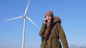 Производство энергии от ветра, довольная девушка говорит телефоном около генераторов энергии ветра акции видеоматериалы