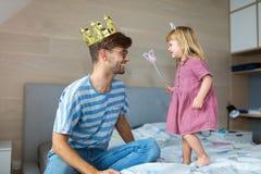 Произношение по буквам дочери бросая на отце с волшебной палочкой стоковое фото rf