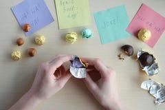 Проказа дня дурачков в апреле Создание программы-оболочки фундука в оболочках конфеты на деревянном столе Шутка с едой стоковое изображение