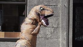 Проказник в костюме rex t в толпе людей идя на тротуар города акции видеоматериалы