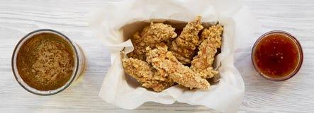 Прокладки предложения цыпленка с соусом и холодным пивом на белой деревянной предпосылке, взгляд сверху Надземный, сверху стоковое изображение rf