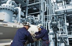 прокладывает трубопровод работники рафинадного завода стоковая фотография rf