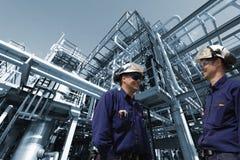 прокладывает трубопровод работники рафинадного завода стоковое изображение rf