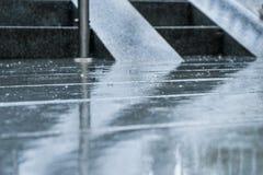 Проливной дождь падает падать на улицу города с лестницами на заднем плане Стоковые Фотографии RF