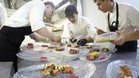 Промежуток времени занятой команды шеф-поваров подготавливая еду в коммерчески кухне сток-видео