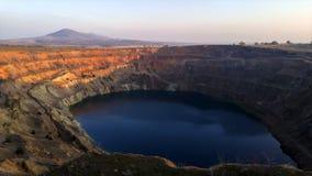 Промежуток времени захода солнца искусственного озера на покинутом кратере шахты акции видеоматериалы
