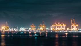 Промежуток времени кранов нагружая контейнеры пересылки в порте грузовых перевозок вечером Импорт или экспорт, логистическая инду