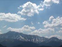 Промежуток времени: пушистые облака неба над снежными пиками гор видеоматериал