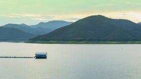 Промежуток времени сплоток плавая в запруду или озеро и облако двигая над горой сток-видео