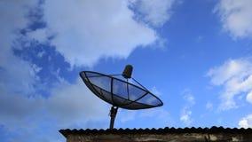Промежуток времени спутниковой антенна-тарелки с предпосылкой голубого неба и облака сток-видео