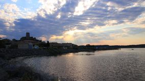 Промежуток времени среднеземноморской деревни Guissan и морского пруда на заходе солнца, Франции сток-видео