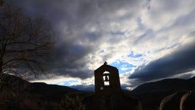 Промежуток времени христианского креста на французском steeple с апоралипсическими облаками