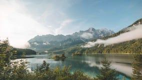 промежуток времени 4K озера Eibsee в Баварии Германии заволакивает во время восхода солнца
