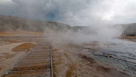 Променад вокруг горячего гейзера горячего источника каскадов и горячее озеро в более низком тазе гейзера в национальном парке Йел Стоковое Изображение RF