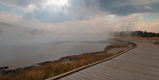 Променад изгибая вокруг горячего горячего источника озера в более низком тазе гейзера в национальном парке Йеллоустона в Вайоминг Стоковые Фотографии RF