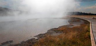 Променад изгибая вокруг горячего горячего источника озера в более низком тазе гейзера в национальном парке Йеллоустона в Вайоминг Стоковое Изображение RF