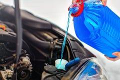 Промывная жидкость экрана автомобиля антифриза женщины лить в пакостный автомобиль Стоковое фото RF