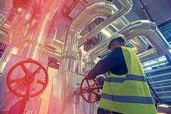 Промышленное заводской рабочий поворачивая красный клапан колеса Стоковая Фотография